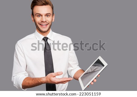 Keep up with technological progress. Cheerful young man holding a digital tablet and pointing it while standing against grey background - stock photo
