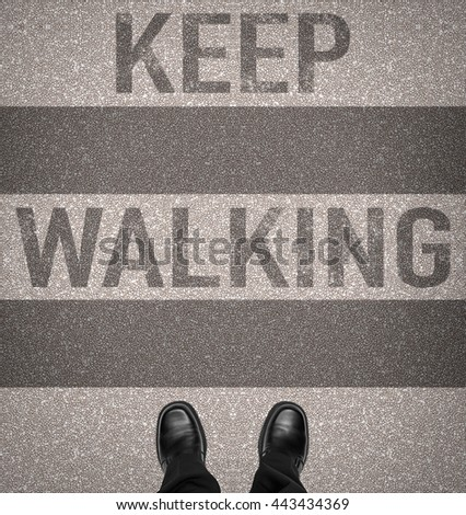 Keep walking message on zebra crossing with business man shoes, overhead view - stock photo