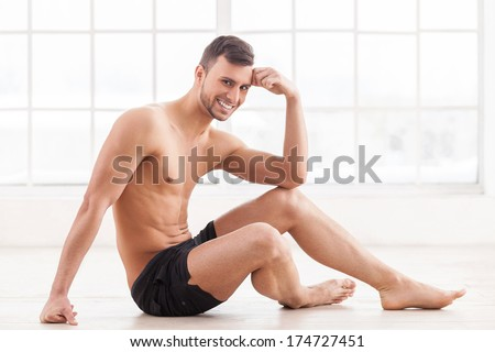 Keeping body in perfect shape. Handsome young muscular man sitting on the floor and smiling