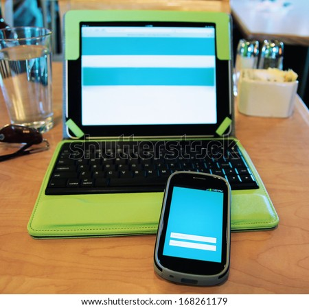 keeping connected with a tablet and a cell phone in a diner (shallow dof - focus on the phone) - stock photo
