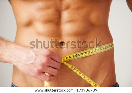 Keeping his body in fit. Close-up of muscular man measuring his waist with measuring tape while standing against grey background - stock photo