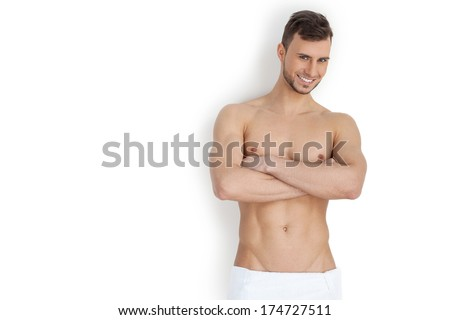 Keeping his body in good shape. Cheerful young muscular man looking at camera and keeping arms crossed while standing isolated on white background - stock photo