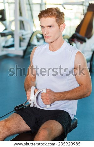 Keeping his boy fit. Concentrated young man working out in gym