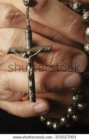 Keeping hold of faith, a man clutches his rosary - stock photo