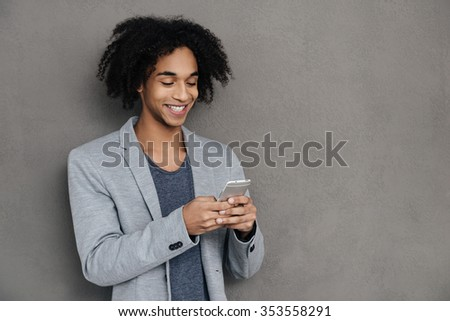 Keeping in touch. Cheerful young African man holding smart phone and looking at it with smile while standing against grey background - stock photo