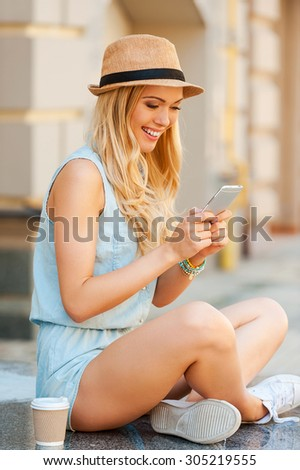 Keeping in touch with her friends. Side view of young woman holding mobile phone and smiling while sitting outdoors - stock photo