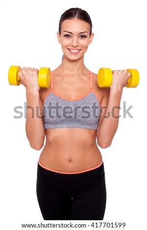 Keeping my body toned. Shot of a beautiful and sporty young woman lifting up weights against white isolated background - stock photo