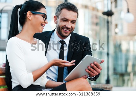Keeping up with the latest news. Low angle view of cheerful young businesswoman pointing at digital tablet while her male colleague holding it - stock photo