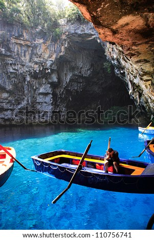 KEFALONIA, GREECE - JUNE 21 - Worker sat in his boat waiting for tourists to arrive in Melissani Cave, Kefalonia Greece.  The cave was discovered in 1951.  21 June 2007 - stock photo