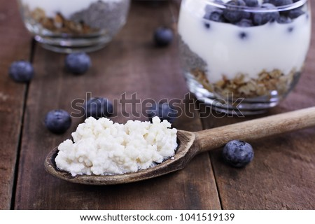 Kefir grains in wooden spoon in front of cups of Kefir Yogurt Parfaits. Kefir is one of the top health foods available providing powerful probiotics.