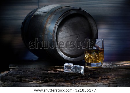 Keg and a glass of whiskey with ice on a wooden table - stock photo
