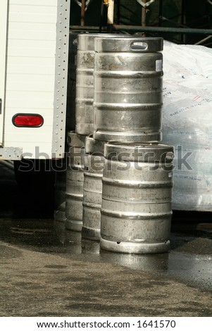 Kegs of beer unloaded from a truck and bags of ice - stock photo