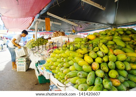 KELANTAN, MALAYSIA-JUN 01: An unidentified street vendor prepares his fruits stalls street market in Kota Bharu on Jun 01, 2013 in Kelantan, Malaysia. Most of the fruits are imported from Thailand