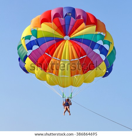 KEMER, TURKEY - AUGUST 18, 2015: Parasailing in a blue sky near sea beach. Parasailing is a popular recreational activity among tourists in Turkey. For editorial use only.