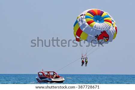 KEMER, TURKEY - AUGUST 13, 2015: Parasailing in a blue sky near sea beach. Parasailing is a popular recreational activity among tourists in Turkey. For editorial use only.