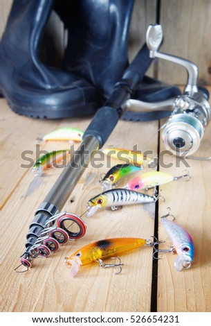 KEMEROVO, RUSSIA - NOVEMBER 29, 2016. Vertical fishing composition with various artificial baits and spinning on wooden background