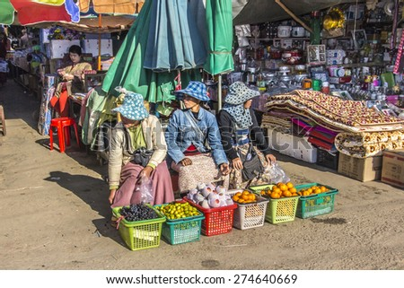 KENG TUNG, MYANMAR - JANUARY 27, 2015: Three myanmar women selling oranges on the market of Keng Tung in the north of Myanmar - stock photo