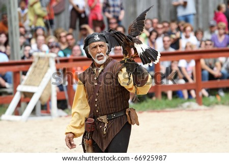 KENOSHA, WI - SEPTEMBER 4: Trainer dressed in medieval costume demonstrates hawks abilities at the annual Bristol Renaissance Faire on September 4, 2010 in Kenosha, WI - stock photo