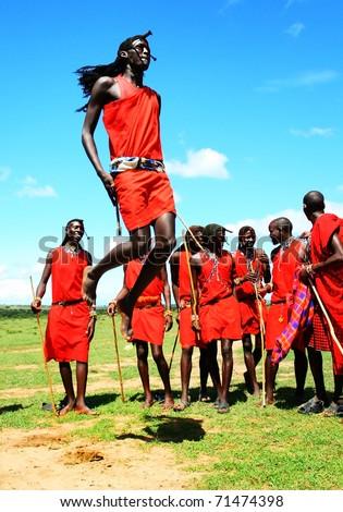 KENYA, MASAI MARA, AFRICA - NOV 12: Masai warriors dance in traditional jumps as a cultural ceremony, near Masai Mara National Park Reserve on November 12, 2008 in Kenya - stock photo