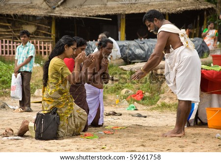 KERALA - AUGUST 9: A hindu priest gives a blessing to commemorate the dead. August 9, 2010 in Kerala, India. Every year, thousands come to Varkala, Kerala to commemorate their ancestors. - stock photo