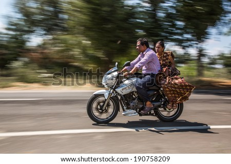 KERALA, INDIA - FEBRUARY 17: Family riding on a bike (blurred motion). Motorbike is the most favorite vehicle and most affordable for India.