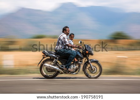 KERALA, INDIA - FEBRUARY 17: Man with child riding on a bike (blurred motion). Motorbike is the most favorite vehicle and most affordable for India.