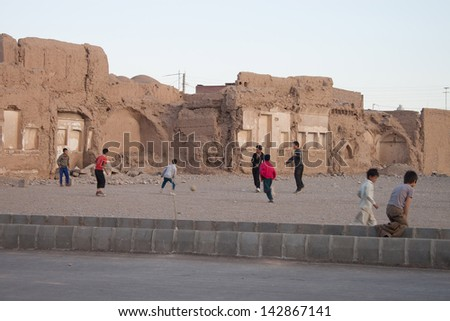 KERMAN, IRAN - MARCH 1: Children play soccer near a ruin of an old building on March 1, 2013 in Kerman, Iran. Population of Kerman is 621,000.