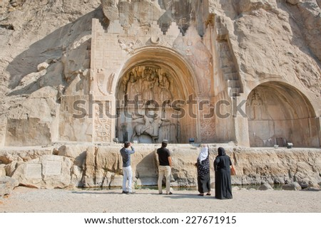 KERMANSHAH, IRAN - OCT 12: Iranian tourists watching the famouse Arches of Taq-e Bostan on October 12, 2014. Taq-e Bostan is a site with large rock relief from the era of Sassanid Empire of Persia