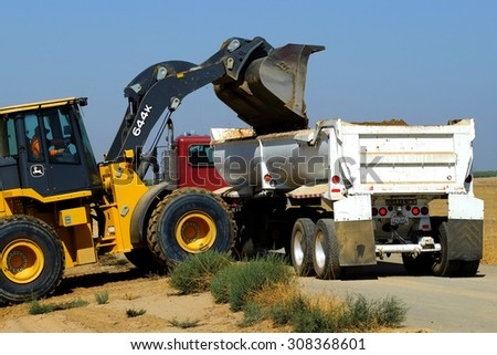 KERN COUNTY, CA - AUG 20, 2015: A front end loader discharges excess dirt from a construction project into a bottom dump truck which will take the material off site. - stock photo