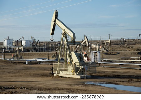KERN COUNTY, CA - DECEMBER 4, 2014: Production is booming in the vast Central California oil fields which rely on secondary recovery techniques (steam and water injection) to bring up the heavy crude. - stock photo