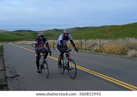 KERN COUNTY, CA - JANUARY 9, 2016: Cyclists from the city climb into the Sierra Nevada Range under winter skies on a training ride in order to regain the fitness lost over the holidays. - stock photo