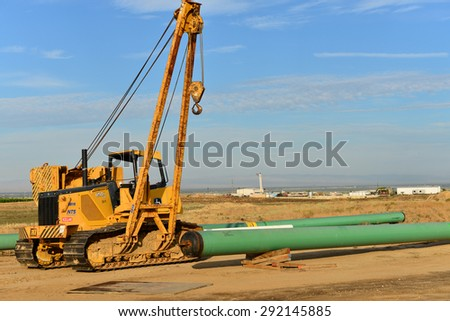 KERN COUNTY, CA - JUNE 27, 2015: Heavy equipment with pipelayer attachment is ready to handle pipe installation in the oil fields. Water and steam piping is used for secondary recovery techniques. - stock photo