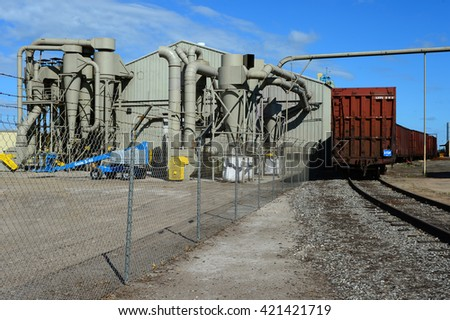 KERN COUNTY, CA -  MAY 15, 2016: Boxcars are lined up on a railroad siding awaiting the loading of fertilizers and agricultural chemicals at a Central California processing plant. - stock photo