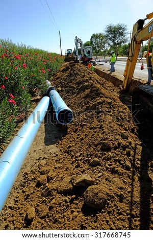 KERN COUNTY, CA - SEPTEMBER 17, 2015: A contractor's personnel, backhoe and other equipment converge to install sewer pipe in a trench paralleling the highway. - stock photo