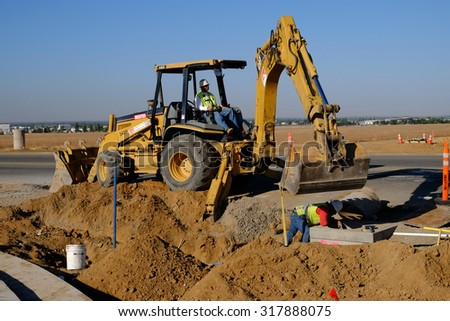 KERN COUNTY, CA - SEPTEMBER 17, 2015: Concrete sewer pipe is guided into place in trench by workman, suspended from the heavy equipment bucket. - stock photo