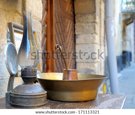 Kerosene lamp and a copper pan on the wooden table - stock photo