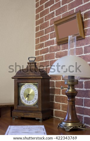 kerosene lamp and old clock on the table. Background - Brick Wall
