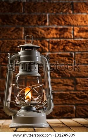 kerosene lamp on brick background - stock photo