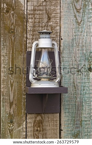 kerosene lamp on the background of the old wooden walls - stock photo