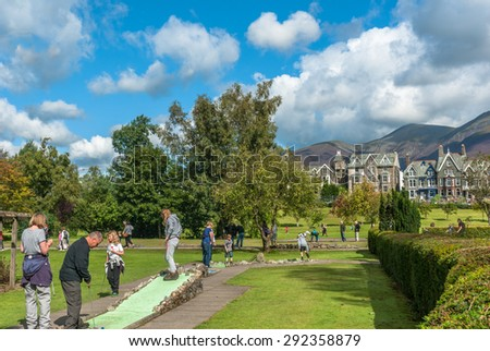 Keswick, UK - AUGUST 22, 2014:People playing crazy golf in Hope Park, Keswick surrounded by the picturesque Cumbrian hills. - stock photo