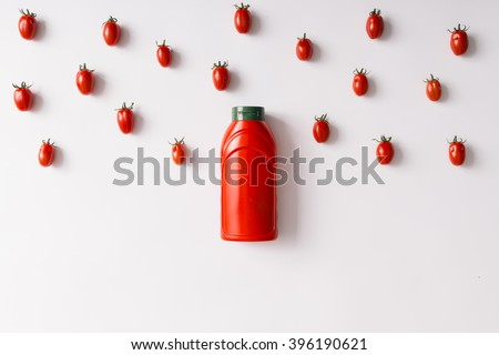 Ketchup bottle concept with cherry tomatoes pattern. Flat lay. - stock photo
