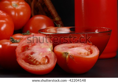 Ketchup in a glass bowl and red bottle surrounded by tomatoes
