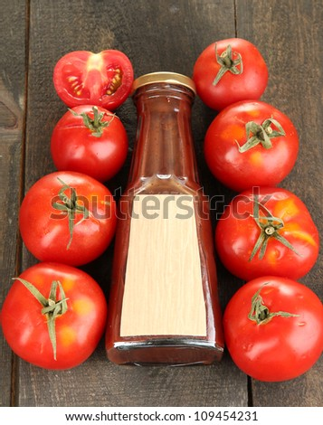 Ketchup in bottle and tomatoes on wooden table - stock photo