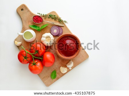 Ketchup or tomato sauce ingredients on a cooking board, concept background, blank space for a text - stock photo