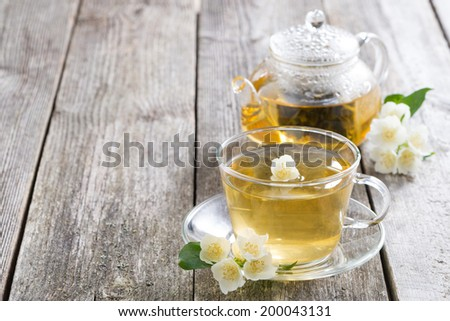 kettle and a cup of green tea with jasmine on wooden background, horizontal - stock photo