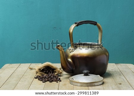 Kettle and coffee beans placed on a wooden table.
