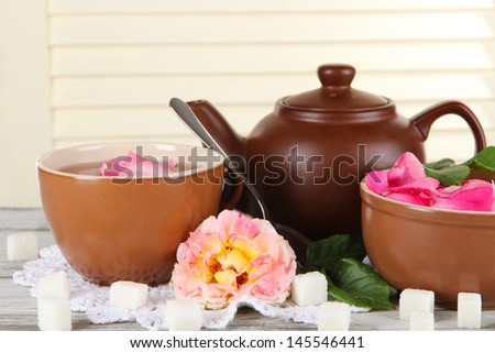 Kettle and cup of tea from tea rose on board on napkin on  wooden background