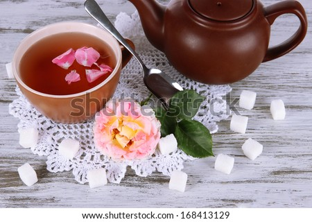 Kettle and cup of tea from tea rose on board on napkin on wooden table