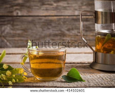 Kettle and cup of tea with linden on wooden background - stock photo