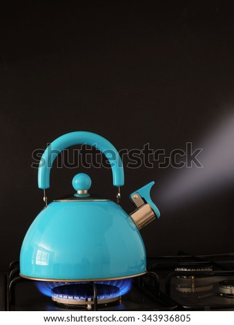 Kettle boiling water on a gas flame kitchen hob